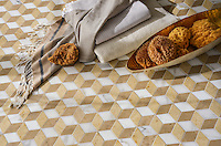 Euclid, a hand-cut shown in polished Calacatta Tia, honed Sylvia Gold, and honed Lagos Gold, is part of the Illusions™ Collection by Sara Baldwin Designs for New Ravenna.