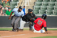 Delmarva Shorebirds catcher Yermin Mercedes (8) puts the tag on Alexander Simon (23) of the Kannapolis Intimidators as home plate umpire Christopher Lloyd looks on at CMC-Northeast Stadium on June 7, 2015 in Kannapolis, North Carolina.  The Shorebirds defeated the Intimidators 9-1.  (Brian Westerholt/Four Seam Images)