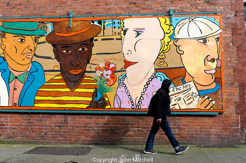 Man walking past a street mural entitled Friends of Post Alley in the Pioneer Square district, Seattle, Washington, USA