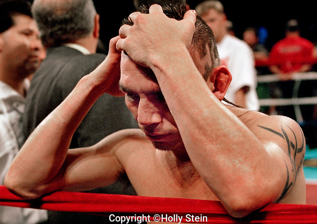 Jorge Paez holds his head after being disqualified in the 5th rd. during his fight with Jose Vida Ramos.