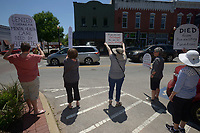 NWA Democrat-Gazette/BEN GOFF @NWABENGOFF<br /> Participants hold their signs for passing motorists to see Sunday, May 7, 2017, during a 'Die-In for ACA' hosted by Ozark Indivisible on the Bentonville square. The group marched around the square and lay down in a 'die-in,' with many holding tombstone-shaped signs carrying personal messages about how healthcare costs and losing coverage for pre-existing conditions could lead to their premature death. The event comes after the U.S. House of Representatives approved legislation Thursday to largely repeal and replace the Affordable Care Act.