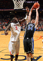 Feb. 16, 2011; Charlottesville, VA, USA; Duke Blue Devils forward Ryan Kelly (34) grabs the rebound in front of Virginia Cavaliers center Assane Sene (5) during the second half of the game at the John Paul Jones Arena. The Duke Blue Devils won 56-41.  Credit Image: © Andrew Shurtleff