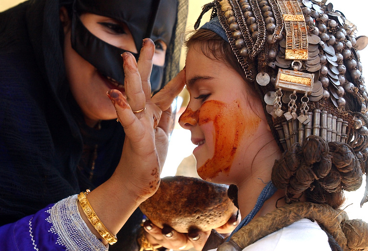 Grace Mitchell, 8, of the District, gets a saffron facial decoration by Najud Hamoud Al Wahibi, in the Oman Desert display, at the Smithsonian Folklife Festival, Thursday, on the Mall.  The mask is donned on special occassions and is also good for the skin,