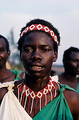 Burundi. One of the Burundi Drummers with red and white headband and necklace, and green and white tunic.
