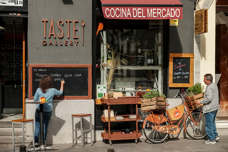 A watchful eye is kept on the street-side restaurant's menu of the day on a quiet street in Madrid.