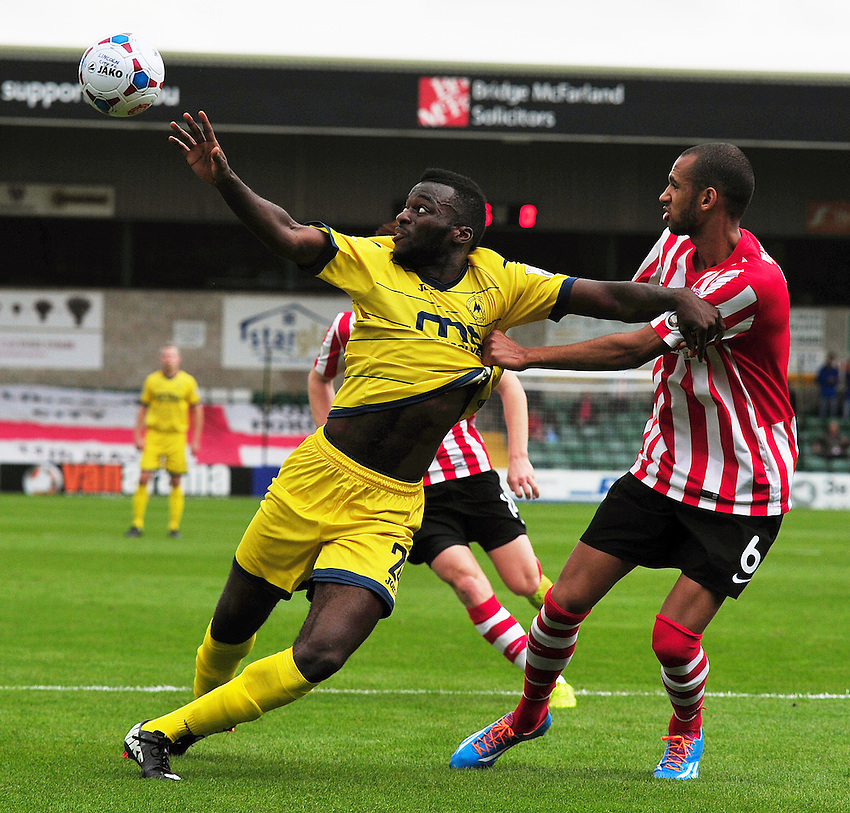 Torquay United's Duane Ofori-Acheampong holds off the challenge from Lincoln City's Tony Diagne<br /> <br /> Photo by Gary Wolstenholme/CameraSport<br /> <br /> Football - English Football Vanarama Conference Premier League - Lincoln City v Torquay United - Saturday 30th August 2014 - Sincil Bank - Lincoln<br /> <br /> &copy; CameraSport - 43 Linden Ave. Countesthorpe. Leicester. England. LE8 5PG - Tel: +44 (0) 116 277 4147 - admin@camerasport.com - www.camerasport.com