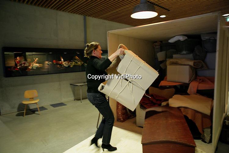 """Foto: VidiPhoto..ARNHEM - In het Nederlands Openluchtmuseum in Arnhem wordt maandagmiddag de laatste hand gelegd aan de inrichting van het thema """"Vaarwel Nederland"""". Het nieuwe seizoen gaat woensdag van start en draait om emigratie van Nederlanders naar andere landen. Via diorama's, en minidocumentaires 'vertellen' emigranten hun geschiedenis. Foto: Het inrichten van een verhuiskist."""