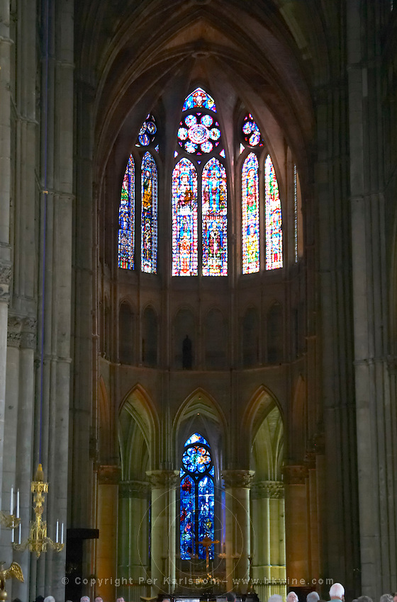 The Reims Cathedral: the stained glass windows behind the altar, the middle one being by Chagall, Reims, Champagne, Marne, Ardennes, France, low light grainy grain