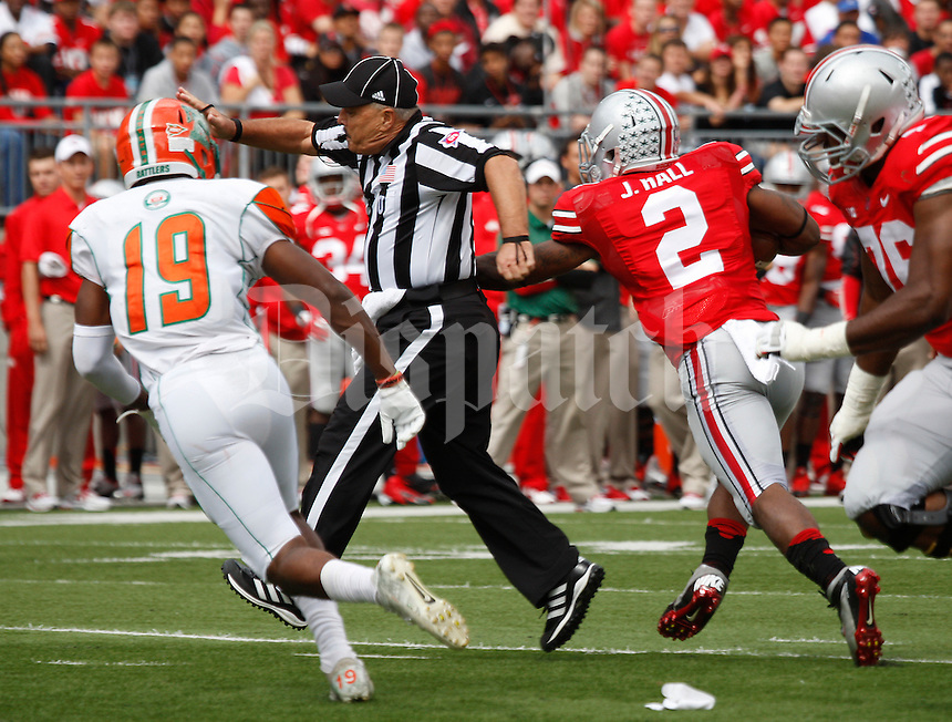 Ohio State Buckeyes running back Jordan Hall (2) runs through umpire Jim Krogstad and Florida A&M Rattlers defensive back Jonathan Pillow (19) on his way to a touchdown during the second quarter of the NCAA football game at Ohio Stadium in Columbus on Sept. 21, 2013. (Adam Cairns / The Columbus Dispatch)