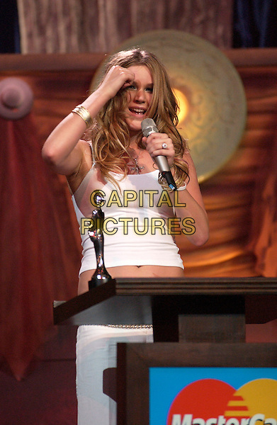 JOSS STONE .Brit Awards 2005.Earls Court 2, London, SW5.February 9th, 2005.half length stage microphone speech touching head white tank top bracelets.www.capitalpictures.com.sales@capitalpictures.com.©Capital Pictures
