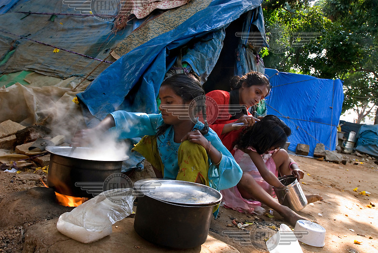 A young girl cooks while her mother brushes her sister's hair outside their makeshift shelter.