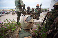 A Somali National Army member sits outside after being shot in the helmet.