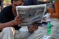 Grecia, Patrasso 2011: rifugiati afghani in un improvvisato campo in una stazione ferroviaria abbandonata. Un immigrato legge un giornale arabo. Grece ville de Patras  2011 - refugies afghans dans une gare abandonnee