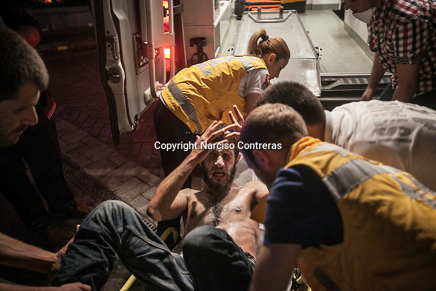 In this Saturday, Jun. 15, 2013 photo, an injured protester is carried out to an ambulance after anti-riot police attacked a peaceful rally in Gezi park of Taksim Square during the ongoing turmoil in Istanbul,Turkey. (Photo/Narciso Contreras).
