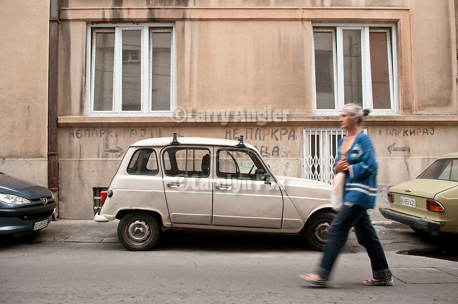A small Zastava  automobile parks in front of a hand-painted No Parking sign on a back street in Belgrade, Serbia.