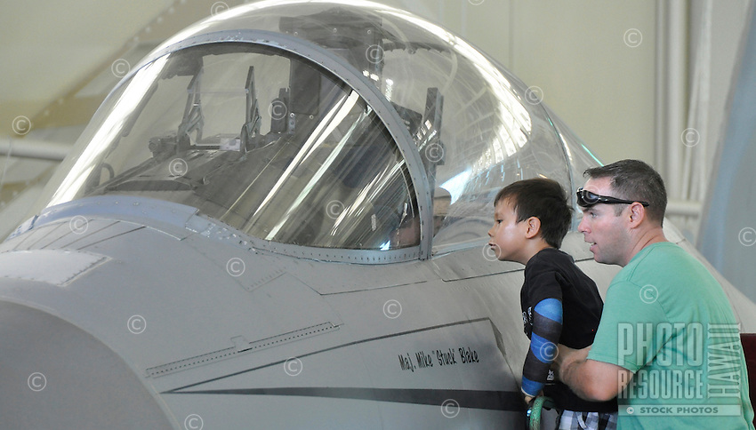 A father lifts up a boy for a better view of the cockpit of a fighter jet at the Pacific Aviation Museum, Ford Island, O'ahu.