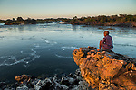 Boy looking over river and waterfalls, Sioma Falls, Zambezi River, western Zambia