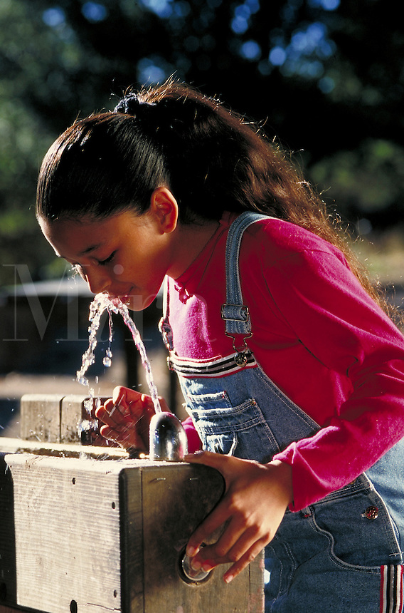 HISPANIC GIRL AT WATER FOUNTAIN. HISPANIC GIRL. SAN FRANCISCO CALIFORNIA USA.
