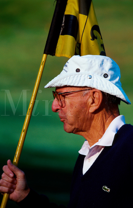 Profile portrait of a senior male golfer as he wears a smug expression while holding a flag for another player.