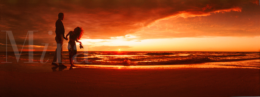 Panoramic of couple walking on the beach at sunset