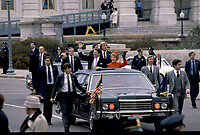Washington, DC., USA, January 20, 1981<br /> President Ronald Reagan and First Lady Nancy Reagan stand up thru the sun roof of their limousine waving to the crowds lining the sidewalks of the Capitol as they leave for the start of their Inaugural parade. Agents from the Secret Service Presidential Protective Detail walk along side the limousine. This is considered a high honor for the members of the United State Secret Service, to walk the entire parade route. Some of these agents also walked along President Reagan's casket as returned to the capitol along this very same route  for his funeral. Credit: Mark Reinstein/MediaPunch