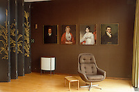 Family portraits by Mather Brown hang in a row on a hessian covered wall behind an armchair designed by Patrick Gwynne