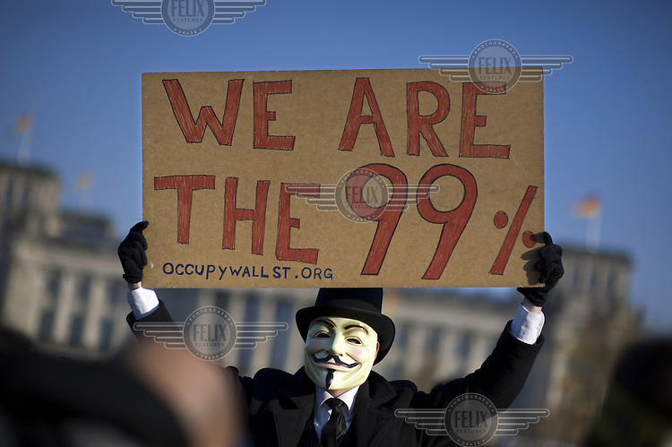 A protestor, wearing a Guy Fawkes mask, one of the icons of the Occupy Movement, outside the Reichstag, holds up a placard that reads: We Are The 99%, during a march linked to the Occupy Movement, a worldwide protest against the banking industry and the prevailing economic system.