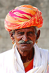 A Rajasthani gentleman wearing a colourful traditional turban and ornate earrings.