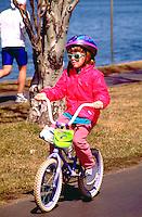 Girl age 7 riding bike around Lake Calhoun.  Minneapolis  Minnesota USA