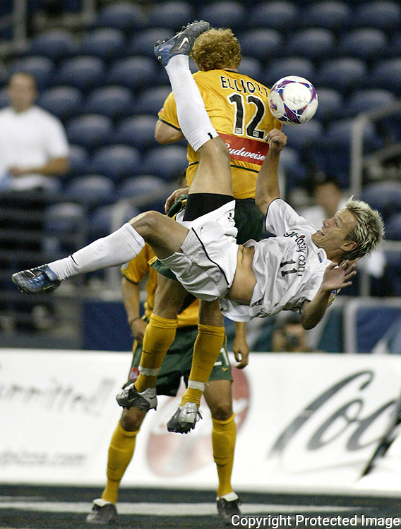 Seattle Sounders' Kyle Smith (11) performs a bicycle kick past L.A. Galaxy's Simon Elliott and towards the Galaxy's goal area during the second half of the 2003 Lamar Hunt U.S. Open Cup Quarterfinals on Wednesday, Aug. 27, 2003 played at Seahawks' Stadium in Seattle. The Galaxy beat the Sounders 5-1 to advance in play.(AP Photo/Jim Bryant)