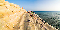 Panoramic photo of Scala dei Turchi, tourists relaxing at sunset, Rossello cape, Realmonte, Agrigento, Sicily, Italy, Europe. This is a panoramic photo of tourists relaxing at sunset on Scala dei Turchi, a limestone cliff known as The Turkish Staircase on the Rossello Cape at Realmonte near Agrigento in Sicily, Italy.