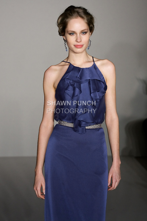 Model walks runway in a French Blue A-line gown, racer neckline, ruffle detail on bodice, natural waist with removable French Blue metallic ribbon belt bridesmaid outfit by Fracesca Pitera for the Jim Hjelm Spring 2012 collection, at the JLM Couture fashion show, during Bridal Week New York Spring 2012.