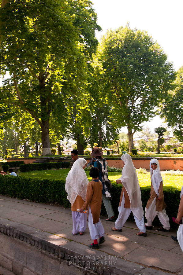 Young Muslim girls in headscarves following a western female tourist and guide through the Nishat Bagh Mughal Garden, Srinagar, Kashmir, India.