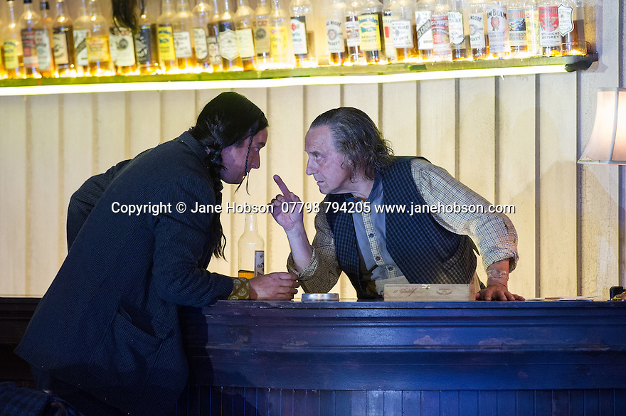 """London, UK. 30.09.2014. English National Opera's production of """"The Girl of the Golden West"""", by Giacomo Puccini, directed by Richard Jones, conducted by Keri-Lynn Wilson, opens at London Coliseum. Picture shows: Jimmy Holliday (Billy Jackrabbit) and Graham Clark (Nick). Photograph © Jane Hobson."""