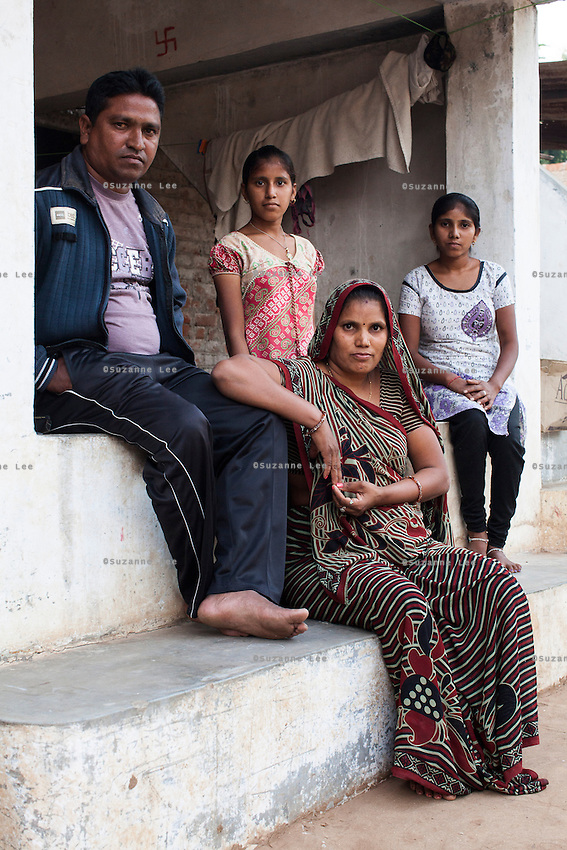 Sharda Solanki, 36, sits for a portrait with her family (from left to right) Kantibhai Solanki, 38, Usha , 15, and Rasmi, 20, in their house in Anand, Gujarat, India on 9th December 2012. While her husband Kantibhai works as a security guard earning 5000 rupees per month, Sharda had made hundreds of thousands with 2 surrogacies that she did with Akanksha Clinic, which she used to buy land, buffaloes, build washrooms in her house and extend the house. She had also saved a substantial amount to fund her 3 children's educations and make sure that her 2 daughters will find husbands to match their current status. Photo by Suzanne Lee / Marie-Claire France