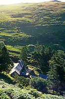 View looking down on the cottage which nestles in a fold of the hills at the end of a steep track