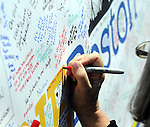 (Boston, Ma 042713) Judy Troncoso adds the comment Boston Strong...USA Forever! as the memorial keeps growing as  thousands of people stop by on Saturday, at the Boston Marathon Bombing  memorial site on Boylston Street in Boston.  (Jim Michaud Photo) for Sunday