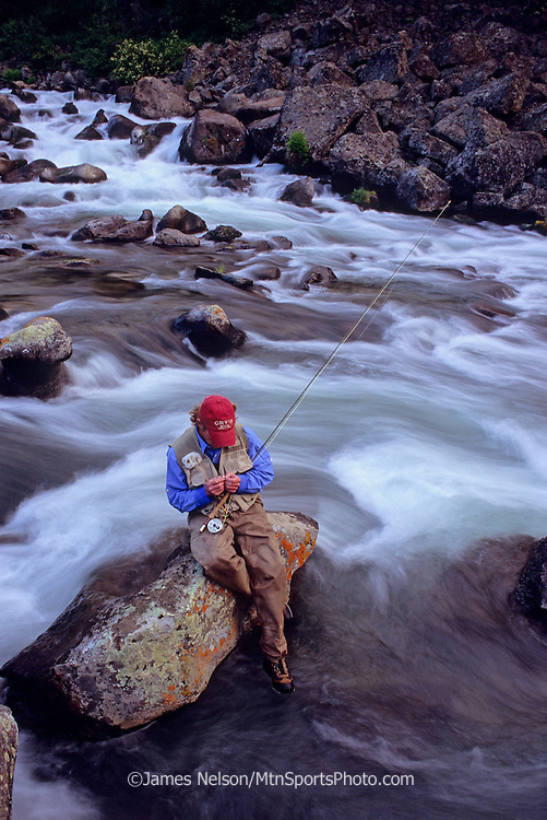 08564-P. An angler ties on a fly while trout fishing on Warm River, Idaho.