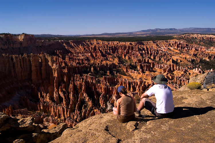 Couple relaxing at Bryce Canyon National Park, Ampitheater and Hoodoos of Silent City from Bryce Point, dawn, erosion, arid, Utah, UT, Southwest America, American Southwest, US, United States, tourists, travelers, sightseeing, no model release, Image ut345-18170, Photo copyright: Lee Foster, www.fostertravel.com, lee@fostertravel.com, 510-549-2202