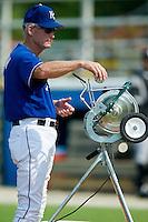 Kansas City Royals roving instructor John Wathan feeds baseballs into a pitching machine at Burlington Athletic Park in Burlington, NC, Thursday, July 12, 2007.