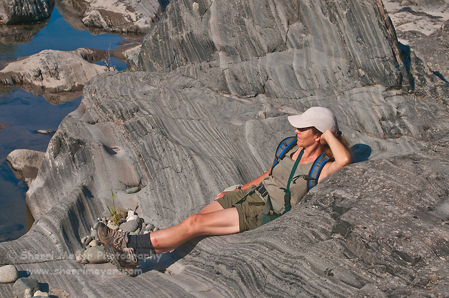 Woman relaxing on a rock, along the North Fork of the American River, Weimar, California.