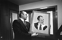 Photograph of President Gerald Ford examining a wood portrait of himself given by Soviet General Secretary Leonid Brezhnev during the Vladivostok Summit Meetings. NOV 1974