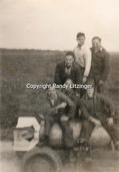 Nick 'Cream' Varella, Sid 'Smuck', Jim Newlands or Walter Gingrow?, C.B. Miller, Eugene 'Porky' Paquette, and Wade Litzinger sitting on top of a 1,000 lb. GP bomb while at CASU 26 NAAF Otis Field at Camp Edwards in Falmouth, MA in Aug., Sept., or Oct 1944.