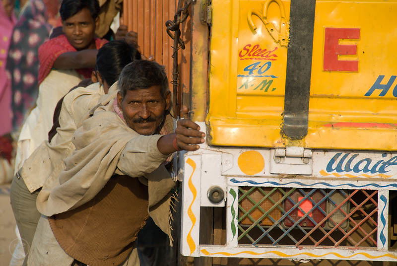 Participants of Janadesh 2007 push the yellow truck on which they are to leave the Gwalior Mela Grounds in New Delhi, trying to get underway on the soft ground, October 2007
