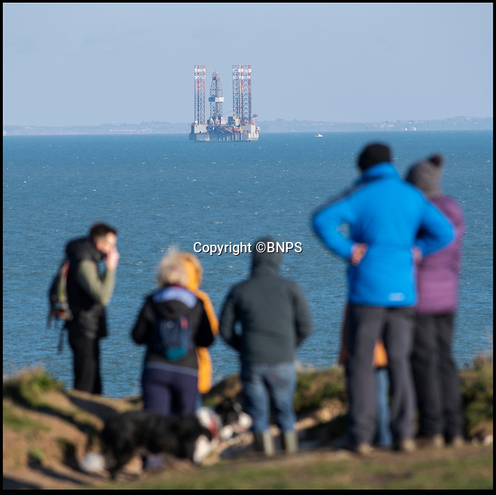 BNPS.co.uk (01202 558833)<br /> Pic: PhilYeomans/BNPS<br /> <br /> Sightseers at Old Harry Rocks on the Jurassic coast near Poole in Dorset were greeted with the sight of a controversial oil drilling platform moving into Poole bay this weekend.<br /> <br /> A controversial oil rig has been positioned between two of Britain's most famous coastal landmarks to begin a test drilling on a deepwater well.<br /> <br /> The ENSCO 72 rig has been given government permission to spend 40 days digging an appraisal well for oil in Poole Bay, Dorset, which forms part of the Jurassic Coast UNESCO World Heritage Site.<br /> <br /> The 340ft high platform stands four miles east of the popular beauty spot of Old Harry Rocks, near Swanage, and 10 miles west of the Needles on the Isle of Wight.<br /> <br /> Its arrival has sparked anger with not only environmentalists but also many residents of Bournemouth who can clearly see the 250ft wide platform from its famous seafront.