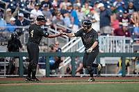 Vanderbilt Commodores outfielder Stephen Scott (19) is greeted by head coach Tim Corbin (4) after his second home run of Game 8 of the NCAA College World Series against the Mississippi State Bulldogs on June 19, 2019 at TD Ameritrade Park in Omaha, Nebraska. Vanderbilt defeated Mississippi State 6-3. (Andrew Woolley/Four Seam Images)