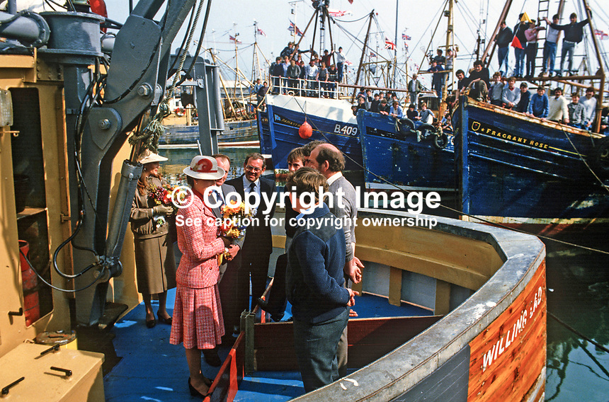 Princess Anne on a May 1985 Royal Visit to N Ireland meets the crew of Willing Lad, a fishing boat in the harbour at Portavogie, Co Down, N Ireland. The crews of other fishing boats get a grandstand view of the visit. Princess Anne had just officially re-opened the harbour after extensive improvements. 19850502f.<br />