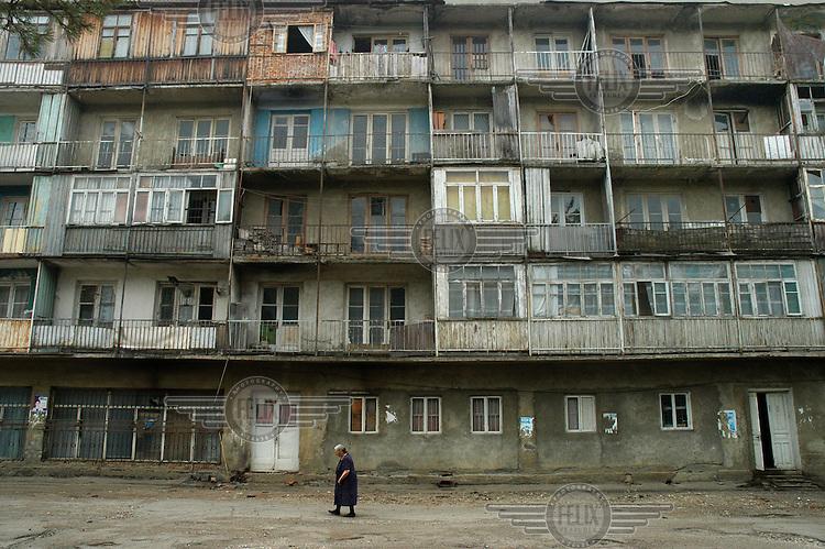 An elderly woman walks by a deteriorating apartment building in Nikidze Shakhta Rayon in Tkibuli.