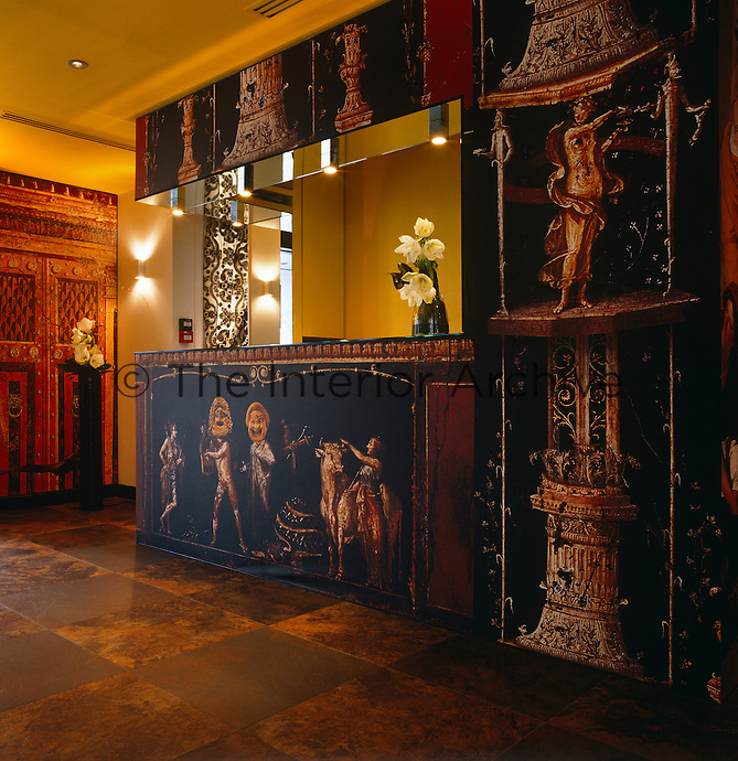 The reception desk is covered in wallpaper with shows an array of classical architectural details with some quirky additions