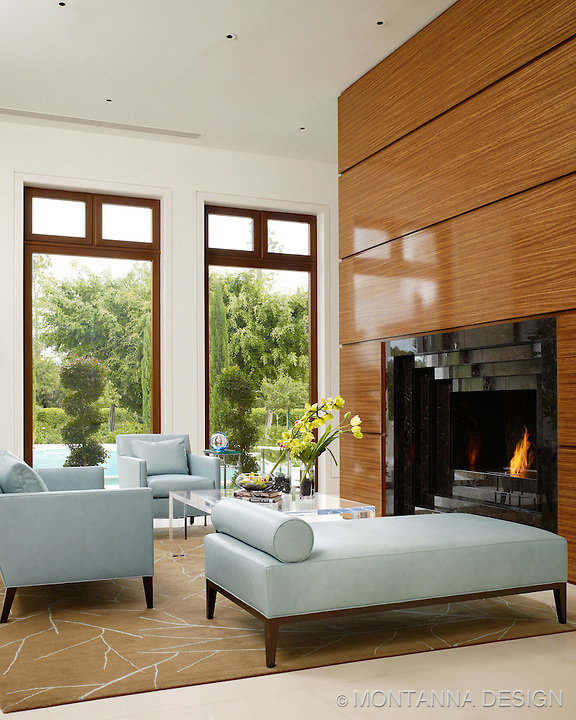 Modern living room with stepped marble fireplace and light aqua blue leather seating